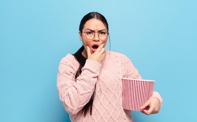 Hispanic frau mit mund und augen weit offen und hand am