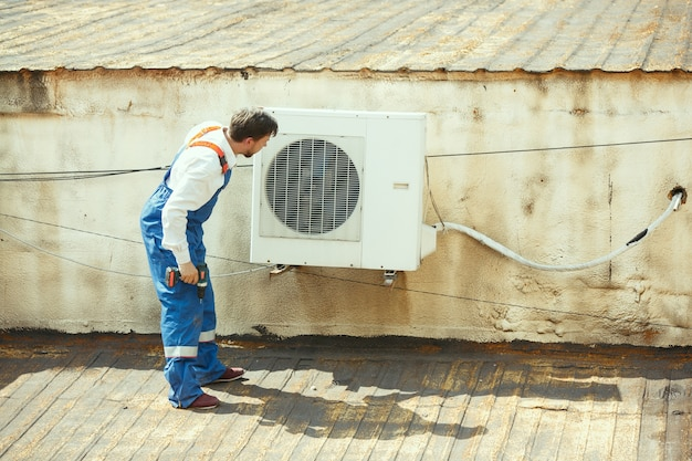 Hlk-techniker, der an einem kondensatorteil für die kondensationseinheit arbeitet. männlicher arbeiter oder handwerker in einem einheitlichen reparatur- und einstellkonditionierungssystem, das technische probleme diagnostiziert und sucht. Kostenlose Fotos