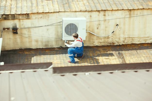 Hlk-techniker, der an einem kondensatorteil für die kondensationseinheit arbeitet. männlicher arbeiter oder handwerker in einheitlichem reparatur- und einstellkonditionierungssystem, diagnose und suche nach technischen problemen. Kostenlose Fotos