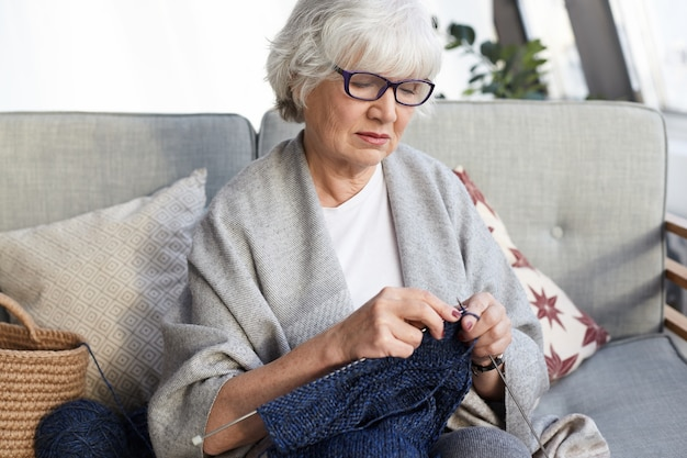 Hobby-, freizeit- und ruhestandskonzept. gut aussehende elegante großmutter mit brille, die auf einer grauen couch mit nadeln sitzt, einen pullover für ihren enkel strickt und einen ernsthaften, konzentrierten blick hat Kostenlose Fotos