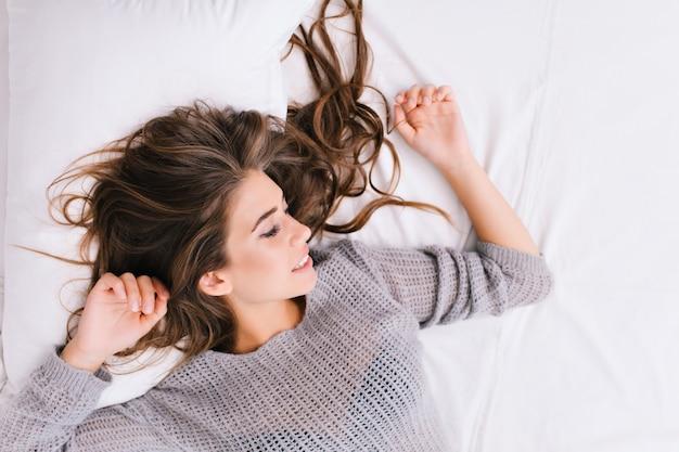 Hoch porträt fröhliches mädchen mit langen brünetten haaren, die auf weißem schlechtem entspannen. guten morgen, positive gefühle, mit geschlossenen augen lächeln, zu hause chillen, träumen. platz für text. Kostenlose Fotos