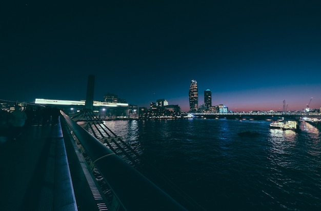 Hoch und stadtgebäude in der ferne von der millennium bridge in der nacht erschossen Kostenlose Fotos