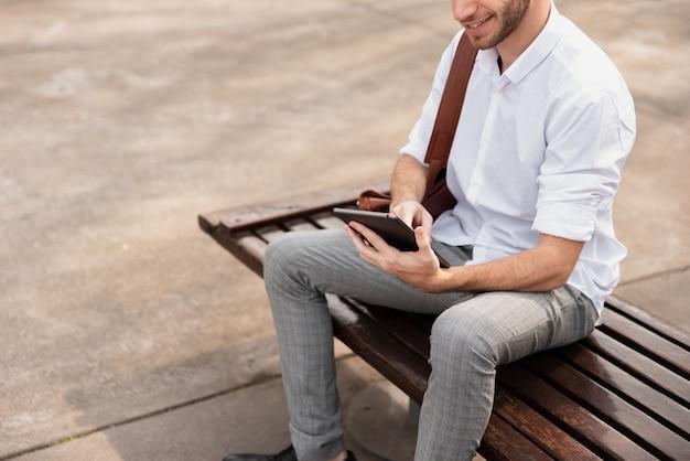 Hochschulstudent, der auf einer bank sitzt und die tablette verwendet Kostenlose Fotos