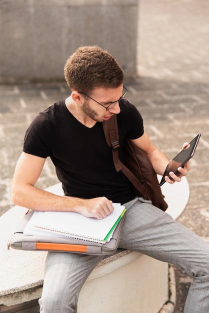 Hochschulstudent, der auf einer bank sitzt und tablette betrachtet Kostenlose Fotos