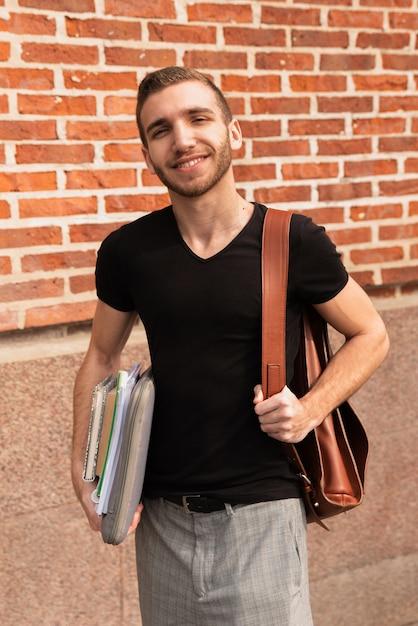 Hochschulstudent mit bemerktem und rucksack lächelnd an der kamera Kostenlose Fotos
