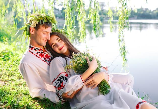 Hochsommer. junge liebespaar in slawischen kostümen am ufer des sees. slawischer feiertag von ivan kupala. Premium Fotos