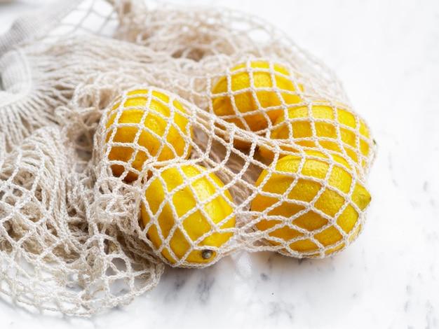 Hochwinkel-baumwollnetzbeutel mit zitrusfrüchten Kostenlose Fotos