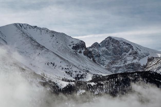Hochwinkelaufnahme der mit schnee bedeckten berge unter dem bewölkten himmel Kostenlose Fotos