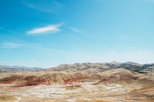 Hochwinkelaufnahme der sandigen hügel in einem verlassenen bereich unter dem hellen himmel Kostenlose Fotos