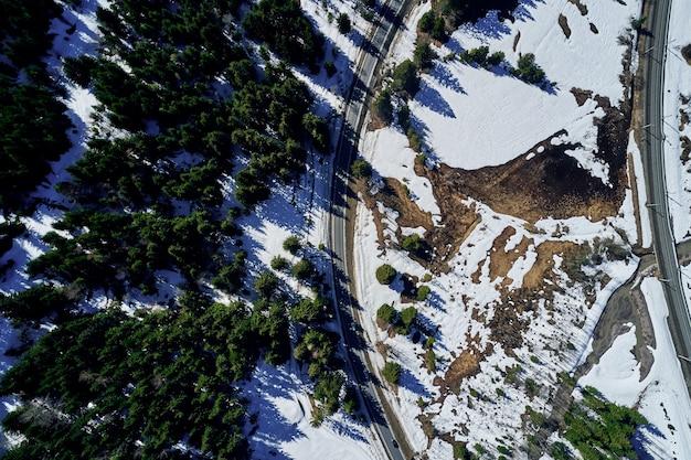Hochwinkelaufnahme einer autobahn in einem schönen fichtenwald im winter mit schnee, der den boden bedeckt Kostenlose Fotos