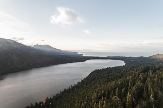 Hochwinkelaufnahme eines flusses in der mitte einer grünen landschaft unter dem klaren himmel Kostenlose Fotos