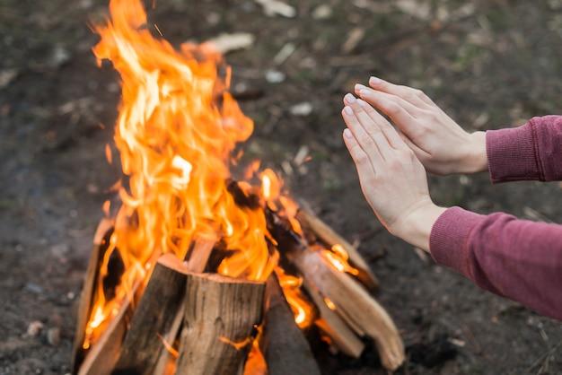 Hochwinkelfrau, die am lagerfeuer wärmt Kostenlose Fotos