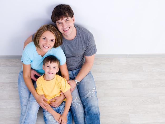 Hochwinkelporträt der glücklichen jungen familie mit dem kleinen jungen, der auf dem boden in lässig sitzt Kostenlose Fotos