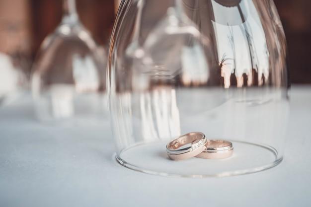 Hochzeit. hochzeitstag. zwei goldhochzeitsringe oben lokalisiert auf weißabschluß. frisch verheiratet Premium Fotos