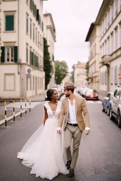 Hochzeit In Florenz Italien Multiethnisches Hochzeitspaar Afroamerikanische Braut In Einem Weissen Kleid Und Kaukasischer Brautigam In Einem Hut Gehen Die Strasse Zwischen Autos Entlang Premium Foto