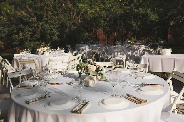 Hochzeitsbankettgedeck verziert mit frischen blumen in einem messingvase Premium Fotos