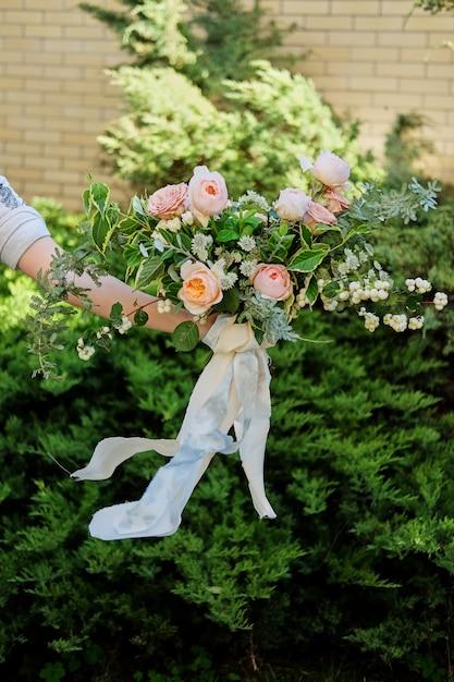 Hochzeitsblumenstrauß in den händen der braut, david austin rose, grüner hintergrund Premium Fotos