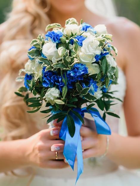 Hochzeitsblumenstrauß mit weißen rosen und blauen blumen in den händen Premium Fotos