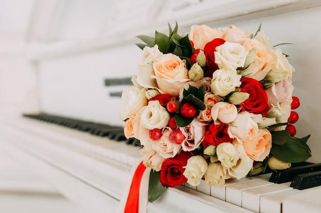 Hochzeitsblumenstrauß von blumen auf einem weißen flügel Premium Fotos