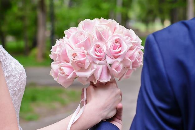 Hochzeitsblumenstrauß von rosa rosen in den händen der braut- und bräutigamnahaufnahme Premium Fotos