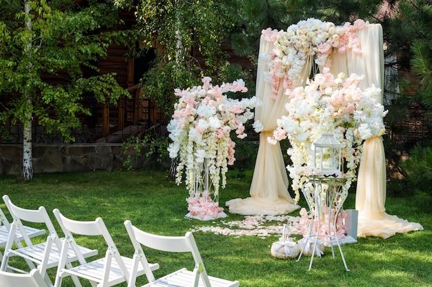 Hochzeitsbogen draußen verziert mit stoff und blumen. Premium Fotos