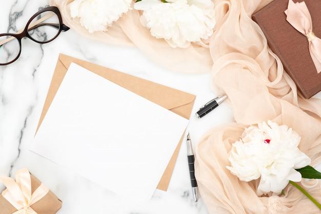 Hochzeitseinladungskarte und kraftpapierumschlag des draufsichtfreien raumes mit weißen pfingstrosenblumen und beige pastellschal. Premium Fotos