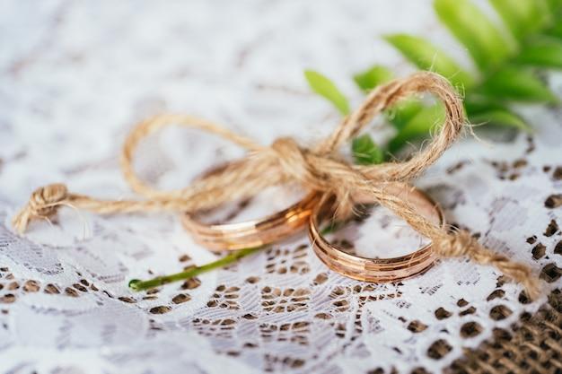 Hochzeitsgoldringe gebunden mit schnur auf rustikalem hintergrund der leinwand und der spitze. Premium Fotos