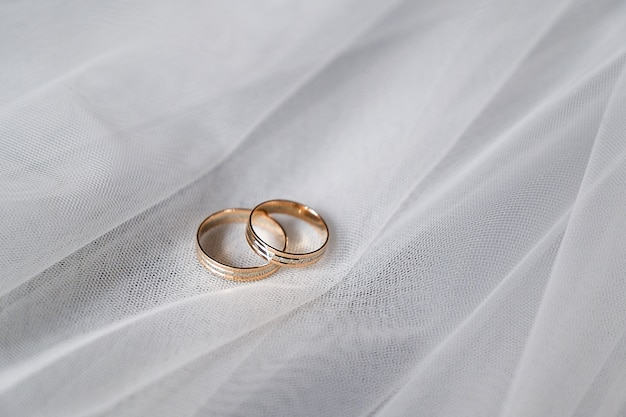 Hochzeitsgoldringe mit edelsteinen auf dem schleier der braut. Premium Fotos
