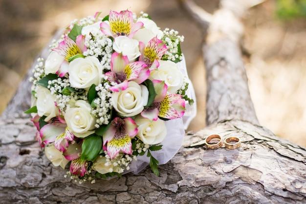 Hochzeitshintergrundblumenstrauß und -ringe auf holz. Premium Fotos