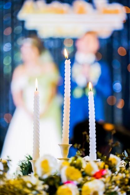 Hochzeitskerze und braut, bräutigam in der zeremonie Premium Fotos