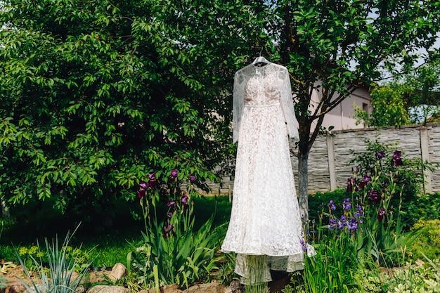 Hochzeitskleid der braut, die im grünen garten hängt Premium Fotos