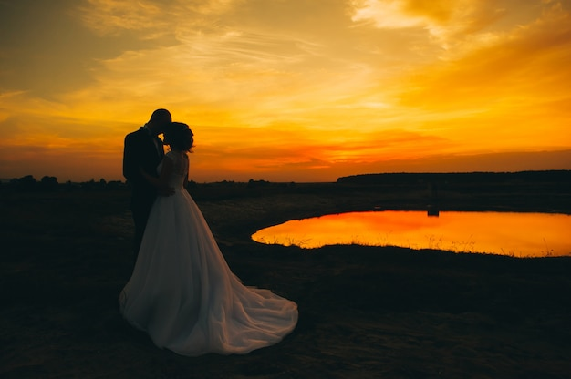 Hochzeitspaar auf dem hintergrund des sonnenuntergangs Premium Fotos