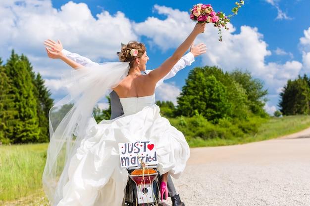 Hochzeitspaar auf dem motorroller gerade geheiratet Premium Fotos