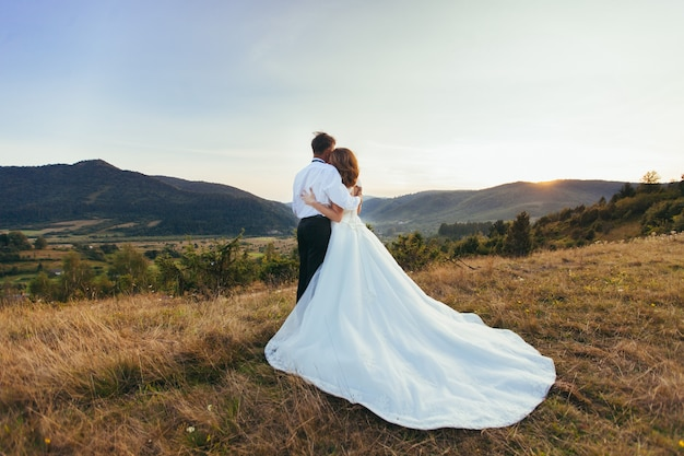 Hochzeitspaar, das auf einem hintergrund des sonnenuntergangs der berge umarmt Premium Fotos