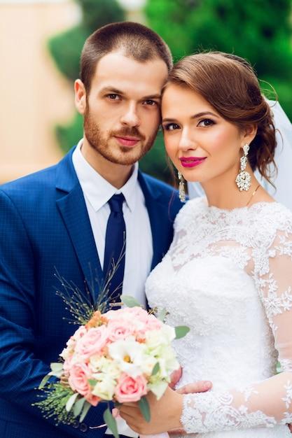 Hochzeitspaar in liebe küssen und lächeln. junge hübsche elegante braut und ihr hübscher bräutigam, der im grünen park aufwirft. Kostenlose Fotos