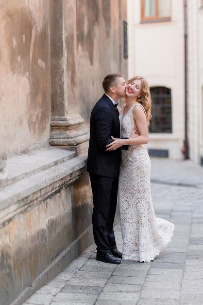Hochzeitspaar küsst draußen in der nähe der wand, glücklich lächelndes paar, wahnsinnig verliebt Kostenlose Fotos