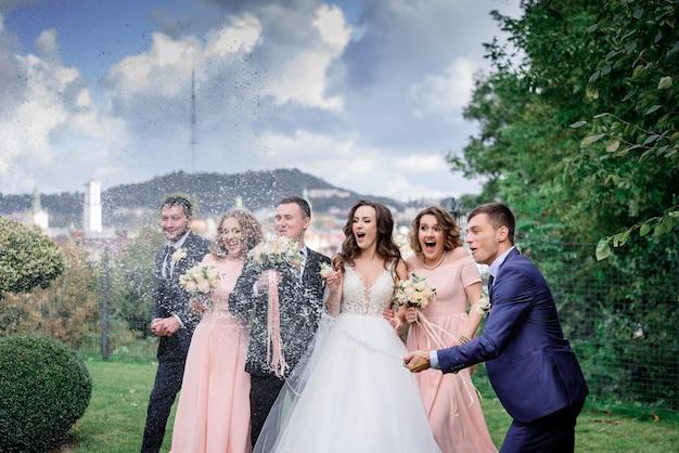 Hochzeitspaar mit besten freunden feiert den hochzeitstag im freien mit champagner Kostenlose Fotos