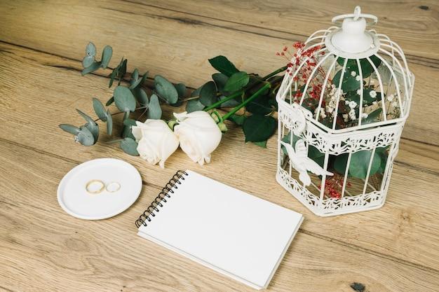 Hochzeitsringe mit blumen und einem notizbuch Kostenlose Fotos
