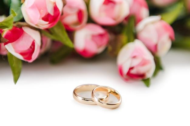 Hochzeitsringe und -blumen getrennt auf weiß Premium Fotos