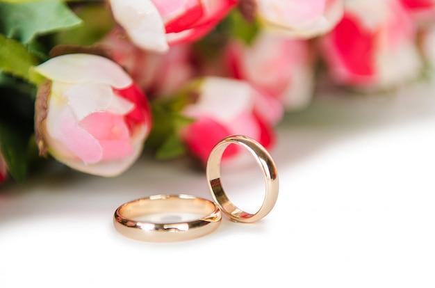 Hochzeitsringe und -blumen getrennt auf weißem hintergrund Premium Fotos