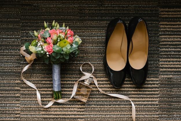Hochzeitsschuhe, birde strauß rosen und eukalyptus, ein glas toilettenwasser Premium Fotos