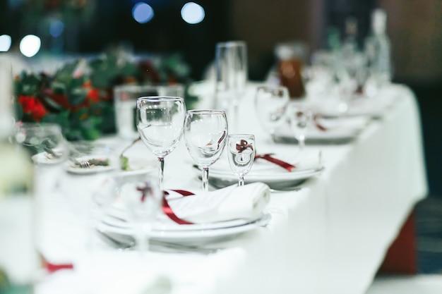 Hochzeitstabelle stellte mit weißen servietten und roten bändern ein Kostenlose Fotos