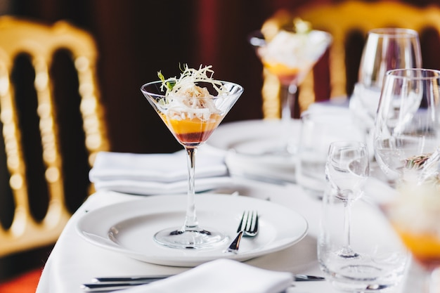 Hochzeitstafel verziert mit weißen platten, gläsern für wein und cocktail in der geräumigen halle Premium Fotos