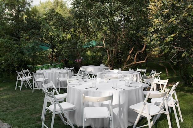 Hochzeitstafeleinstellung verziert mit frischen blumen in einem messingvase. hochzeitsfloristik. banketttisch für gäste im freien mit blick auf die grüne natur. blumenstrauß mit rosen-, eustoma- und eukalyptusblättern. Premium Fotos