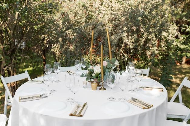 Hochzeitstafeleinstellung verziert mit frischen blumen in einem messingvase. Premium Fotos