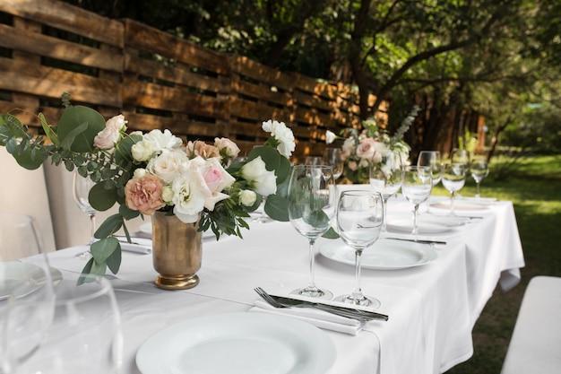 Hochzeitstafeleinstellung verziert mit frischen blumen in einem messingvase Premium Fotos