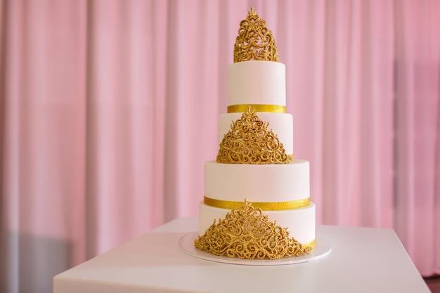 Hochzeitstorte, auf weißer tabelle. 3-stufig mit elfenbeinfondant überzogen, mit perlenspray und goldenen rosen aus zuckerpaste besprüht. hochzeitstorte mit gold Premium Fotos