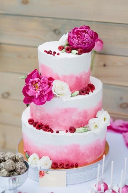 Hochzeitstorte mit blumendekoration und rosa creme. Premium Fotos