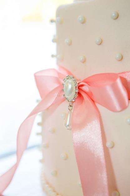 Hochzeitstorte mit weißer zuckerglasur und rosa bogen Premium Fotos