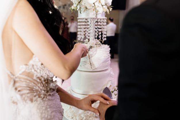 Hochzeitszeremonie des kuchenausschnitts mit bräutigam und braut Kostenlose Fotos